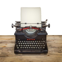 Old typewriter on a vintage wooden floor isolated on white