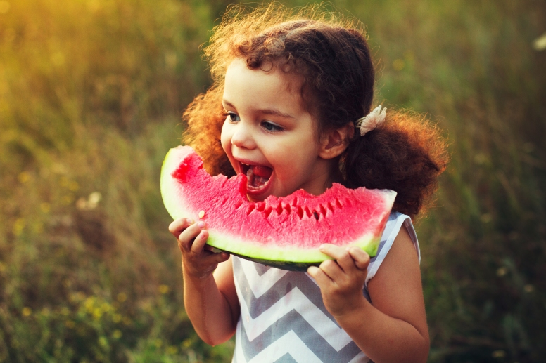 Funny portrait of an incredibly beautiful curly haired little girl eating watermelon, healthy fruit snack, adorable toddler child with curly hair playing in a sunny garden on a hot summer day